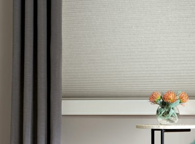 soft white cellular shades layered with gray draperies in Houston TX