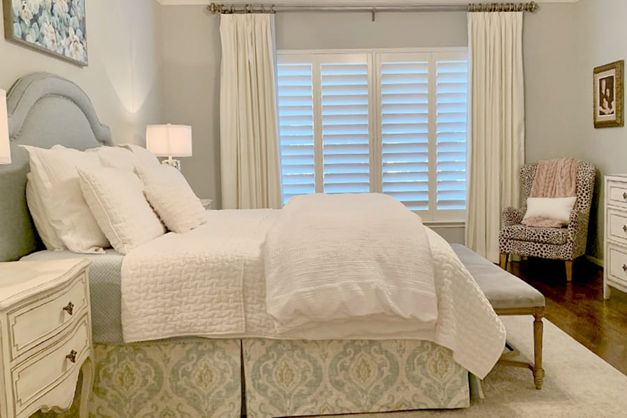 bedroom with white shutters and white drapery panels Friendswood TX