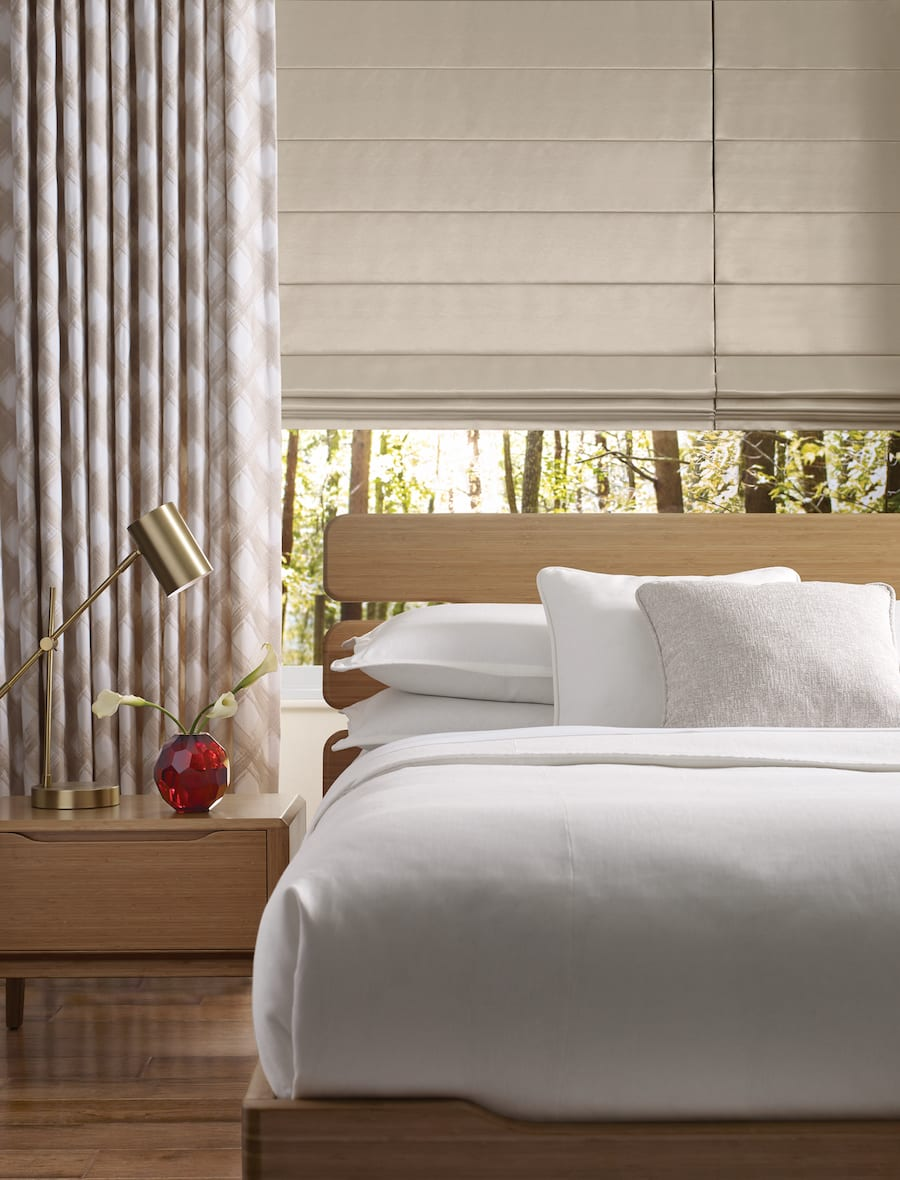 beige roman shades with patterned draperies in houston TX bedroom