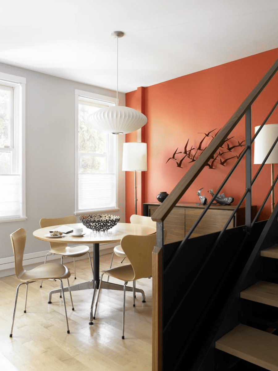 rust accent wall in contemporary dining room