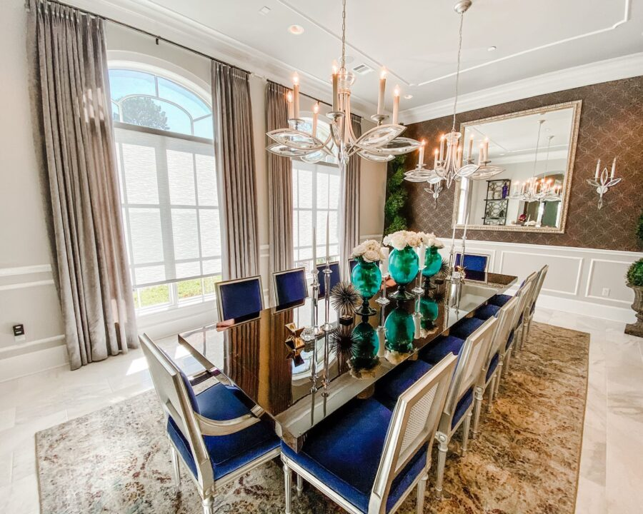 dining room with large arched windows featuring layered draperies and roller shades in Magnolia TX