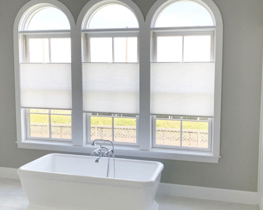 three arched windows in bathroom with white roller shades in Houston TX