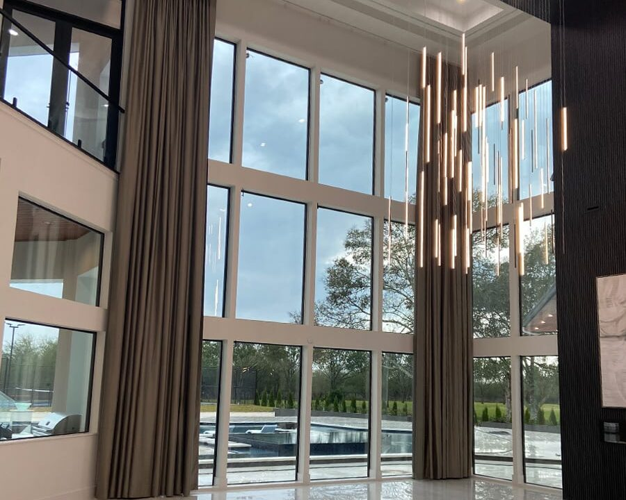 29 foot tall draperies on floor to ceiling windows in paradise in houston home