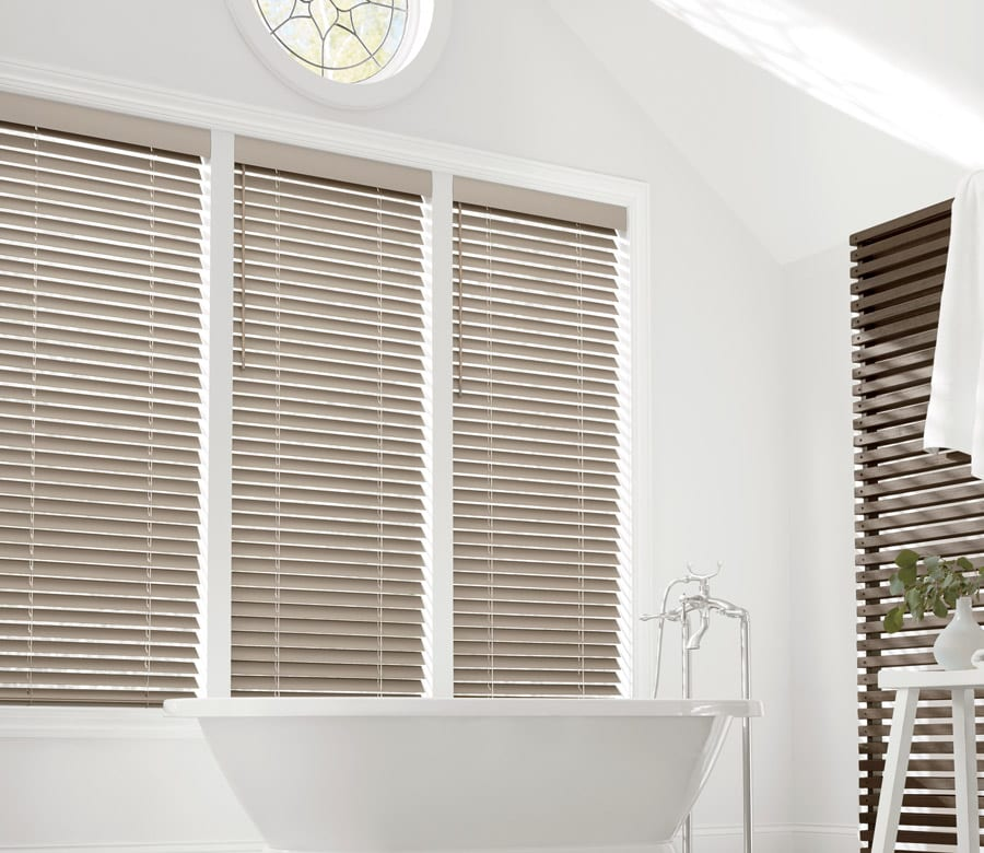 modern bathroom with three windows over tub with neutral faux wood blinds in Magnolia TX