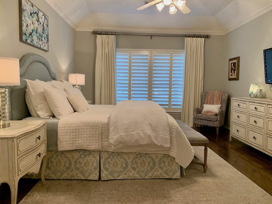 bedroom in Houston with shutters and drapery on windows for relief for houston