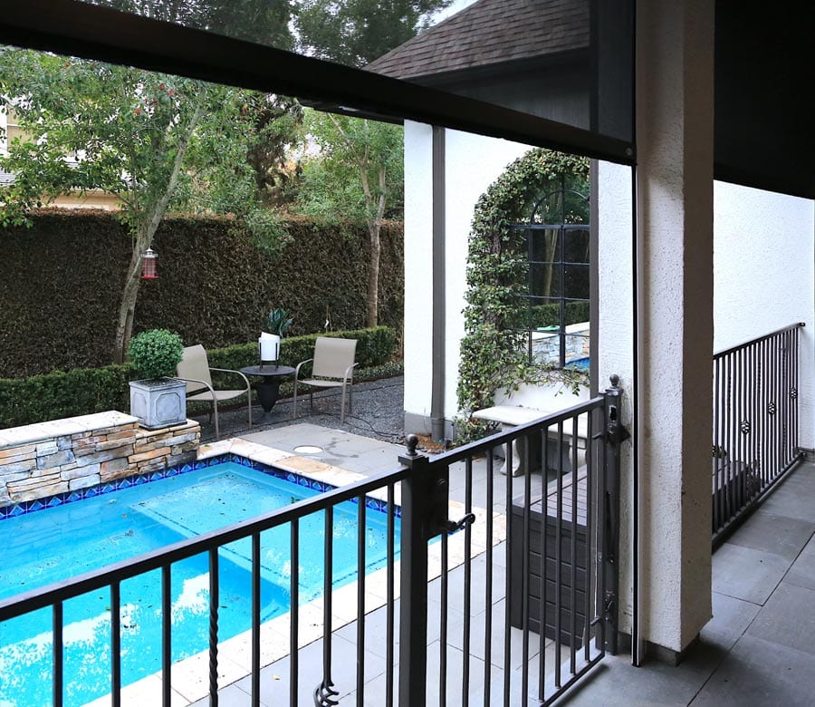 exterior shades on second story patio by pool at Friendswood TX home