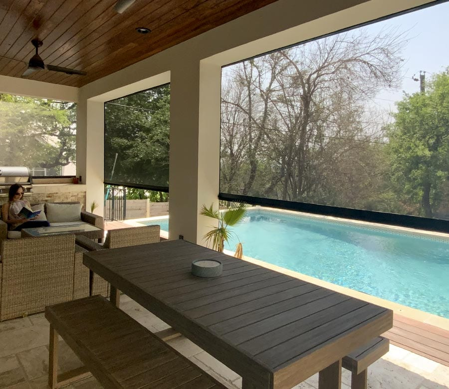 exterior patio shades half lowered by pool in Houston TX