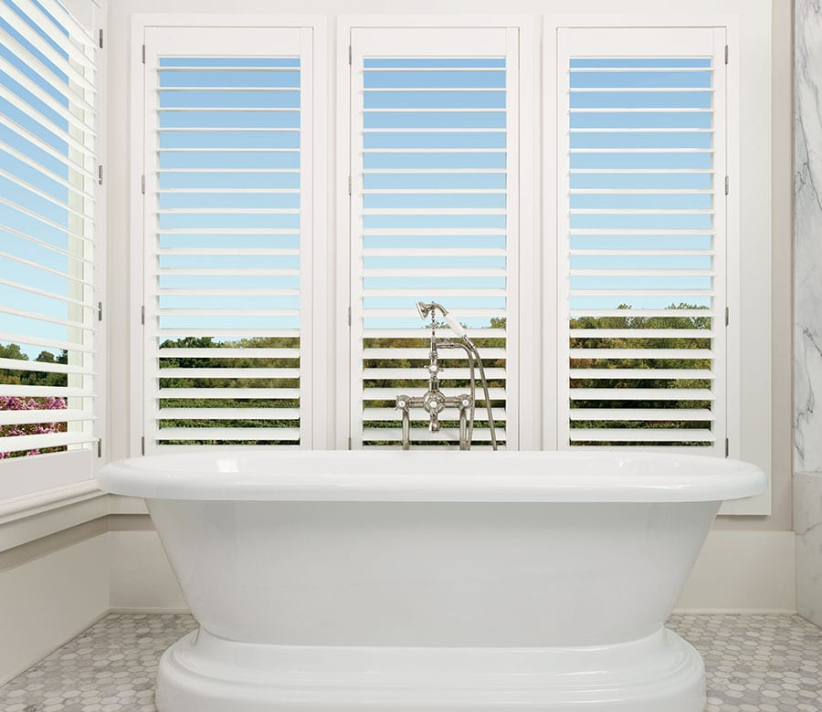 large bathroom windows with motorized palm beach shutters in houston TX