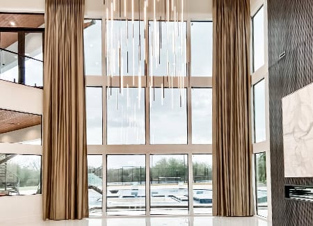 high ceilings wall of windows with draperies