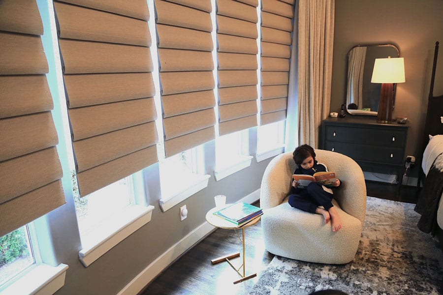 wall of windows in master bedroom covered with roman shades in Houston TX