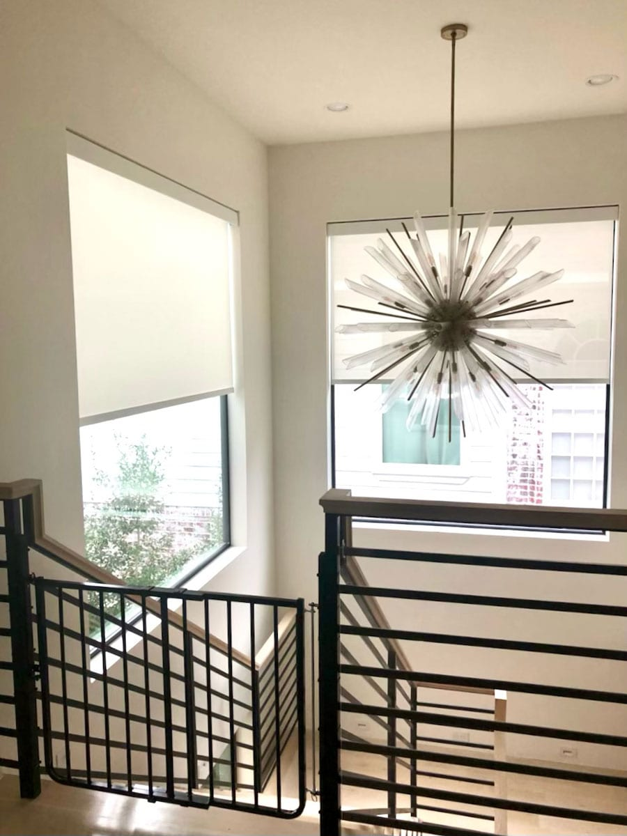 staircase in Friendswood TX with modern chandelier and roller shades