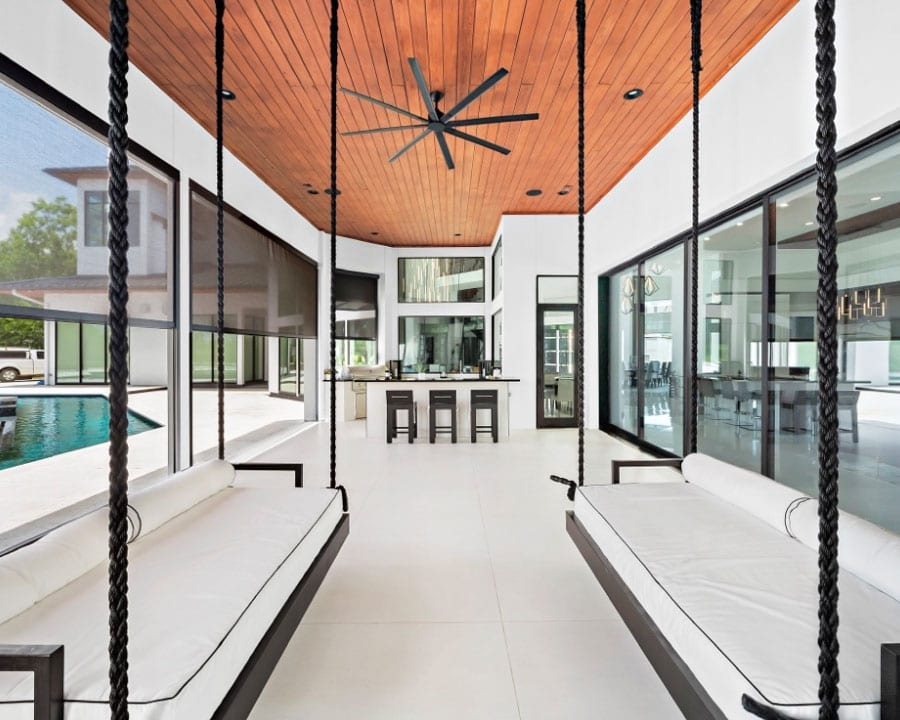 interior of sunroom with grey blinds raised to show outdoor pool