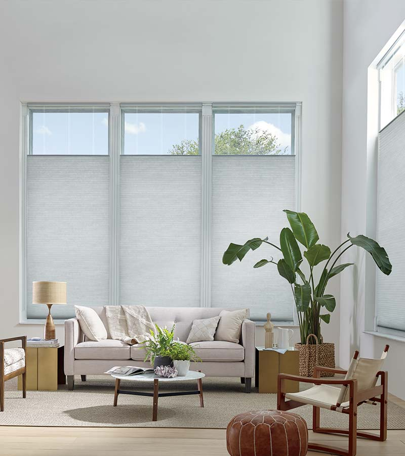 light gray honeycomb shades in Houston TX living room with tops lowered down and window covered