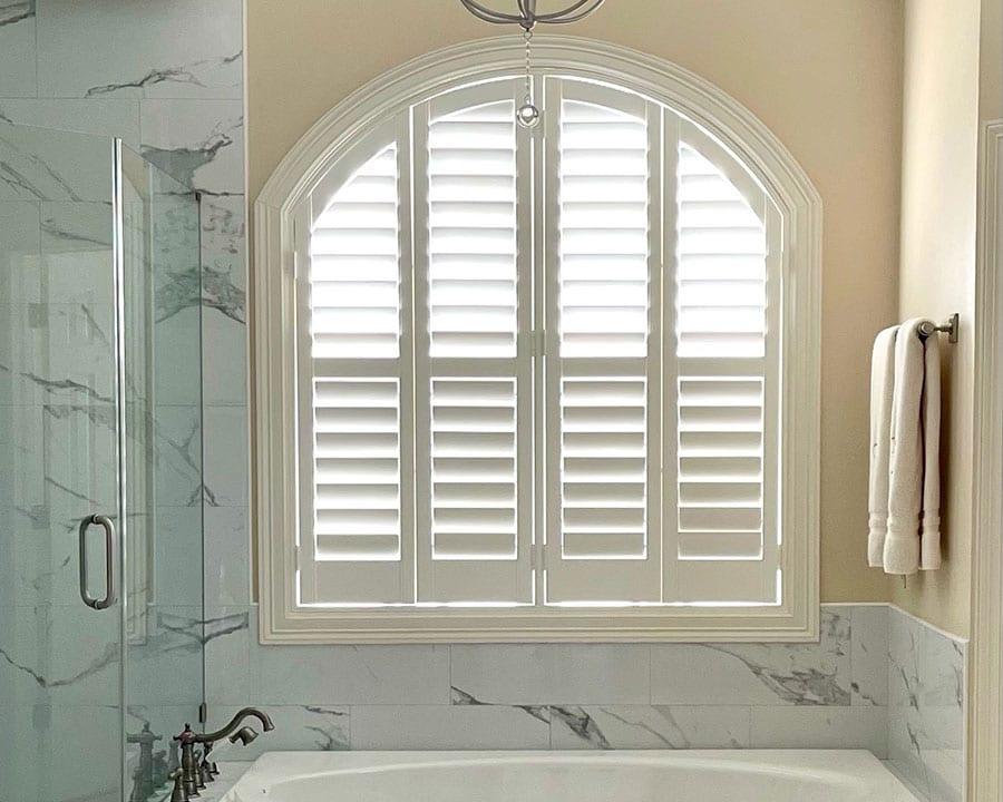 white marble glass shower and sunken tub facing white plantation shutters in Houston TX