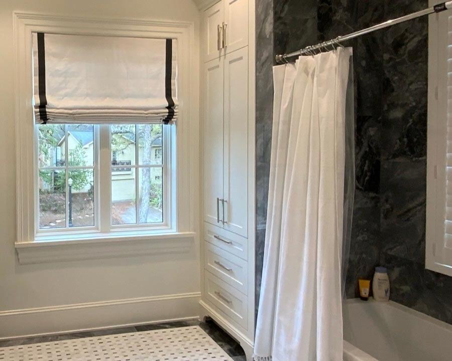 black marble shower in white bathroom with custom drapery in Houston TX