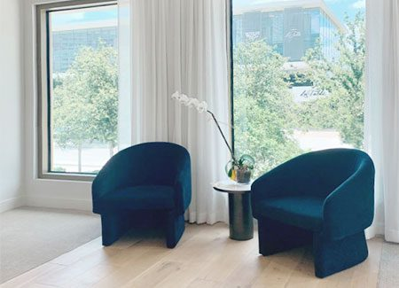 zadok jewelry store white floor to ceiling drapery with blue modern chairs