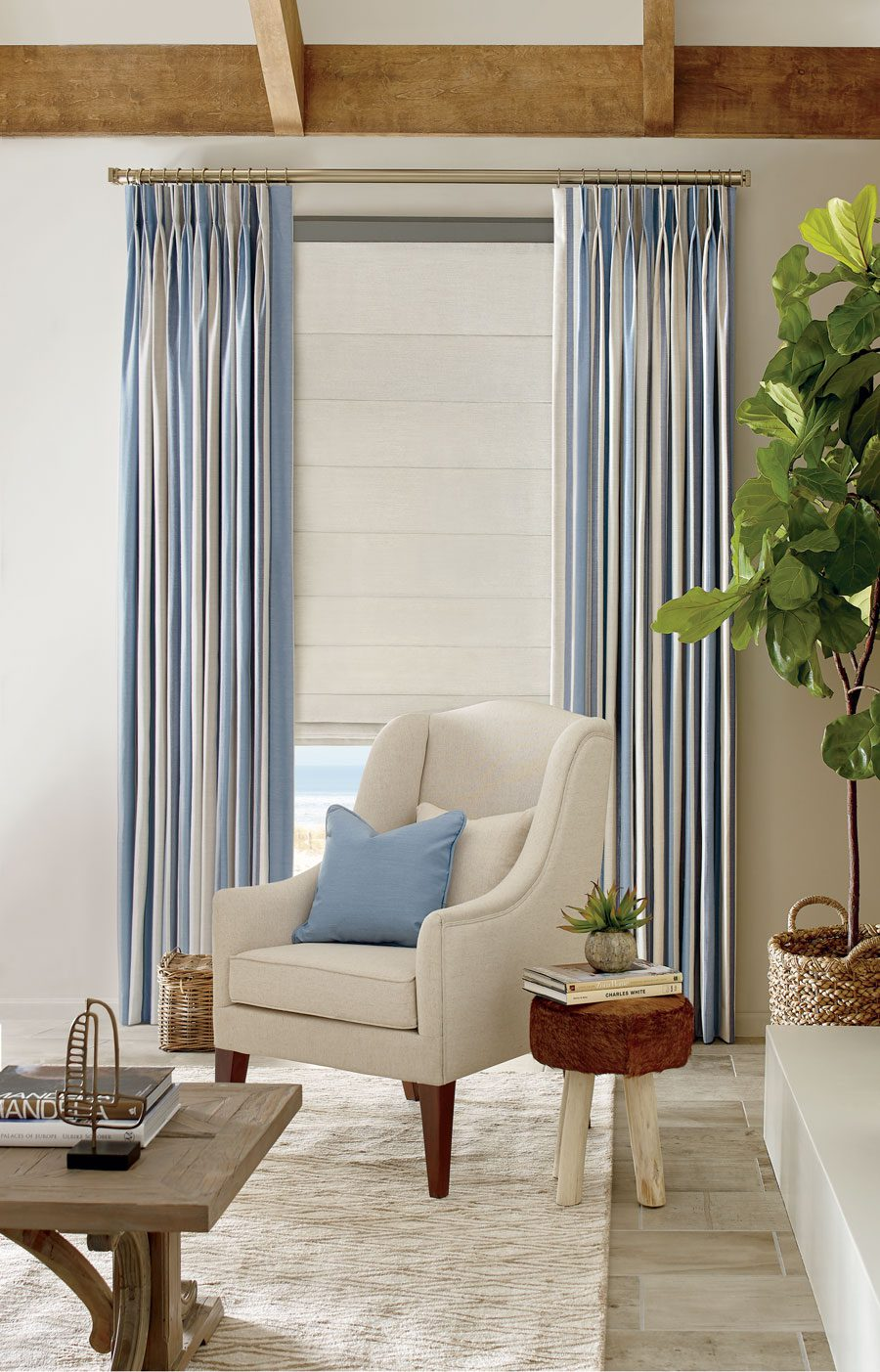 blue striped drapery panels with white fabric roman shades in Houston living room