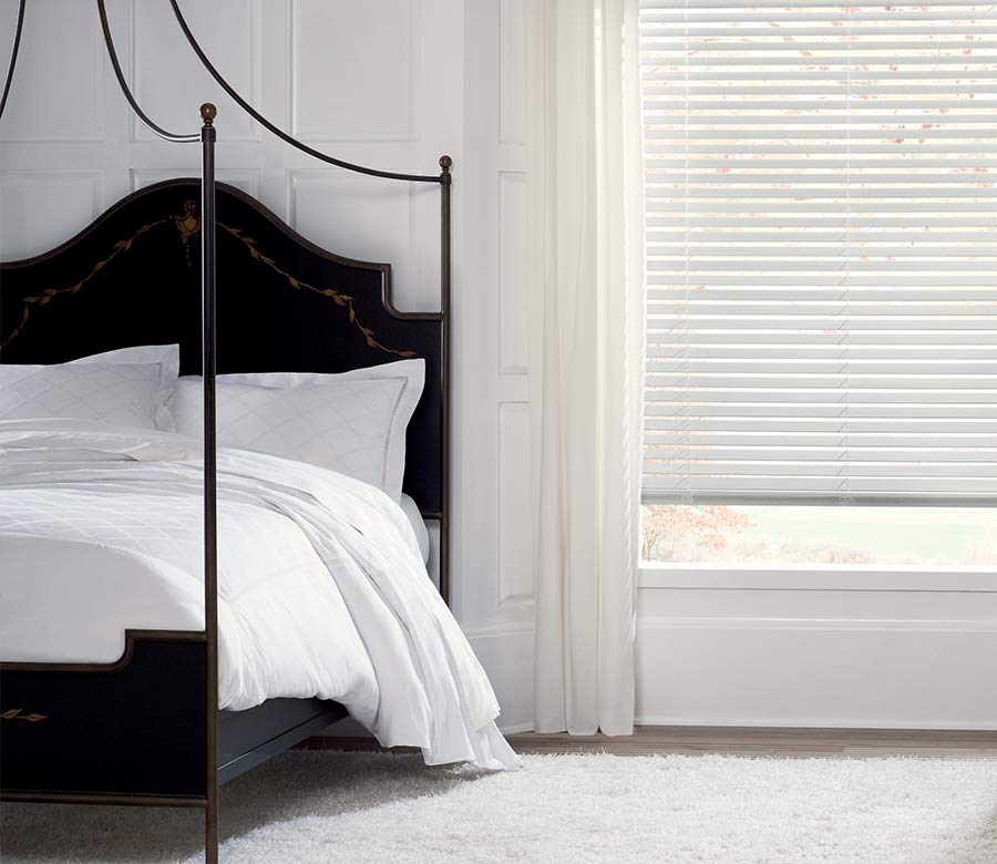 minimalist white bedroom with white wood blinds in houston, tx
