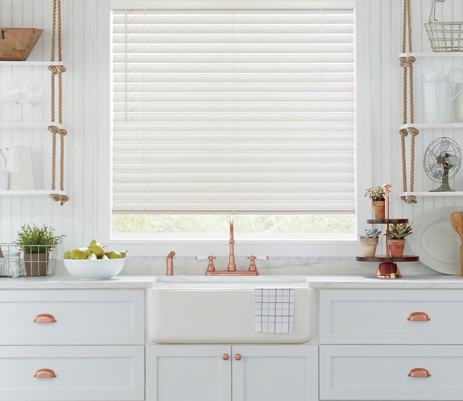 white kitchen with rose gold accents with white wood blinds