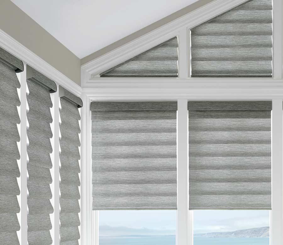 gray roman shades frames by white wood beams in corner window